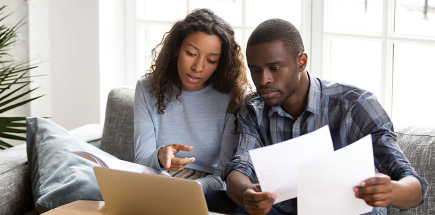 Serious African American couple discussing terms of their mortgage agreement